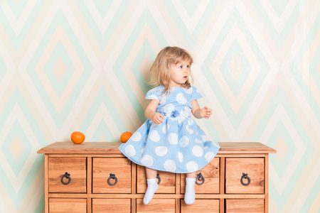 A little baby girl in her room sitting cross-legged on chest of drawers with tangerines on the rhomb wallpaper background. Child in blue polka dot dress and white socks attentively looking aside Reklamní fotografie