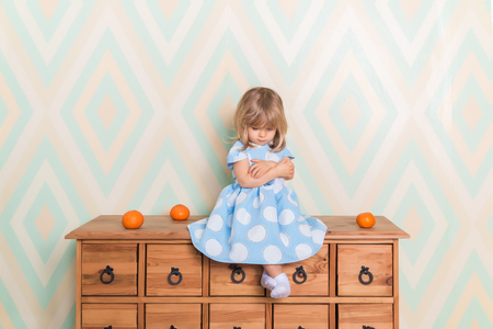 Little baby girl in room sitting cross-legged and cross-arms on chest of drawers with tangerines on rhomb wallpaper background. Child in blue polka dot dress and white socks attentively looking down