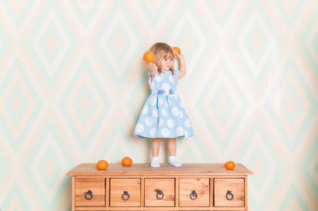 Toddler child girl in blue dress standing on wooden chest of drawers and holding fresh orange mandarins in her hands and going to throw them on rhomb wallpaper background. Winter holidays or christmas