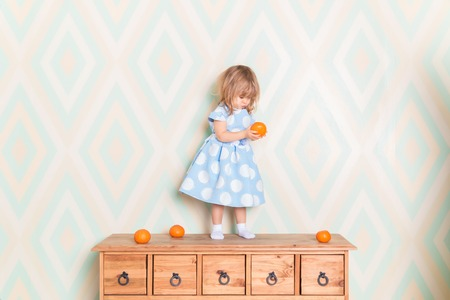 Toddler child girl in light blue dress standing on wooden chest of drawers and holding fresh orange mandarin in hand and looking at it in surprise stretching her lips on rhomb wallpaper background Reklamní fotografie
