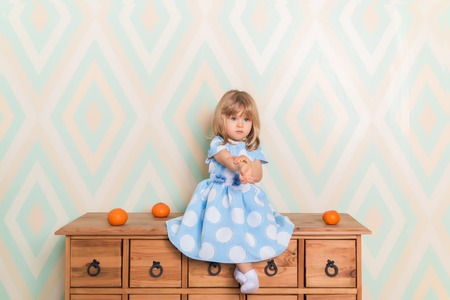 A little baby girl in her room sitting cross-legged on chest of drawers with tangerines on the rhomb wallpaper background. Child in blue polka dot dress and white socks attentively looking down