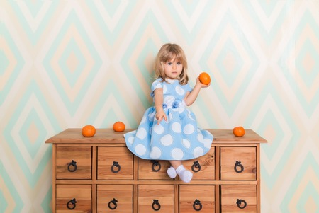 Little baby girl sitting cross-legged on chest of drawers holding tangerine in hand and pointing down with index finger on rhomb wallpaper background. Child in blue polka dot dress and white socks
