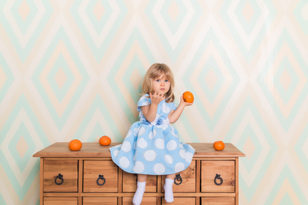 Toddler child baby girl in light blue dress sitting on the wooden chest of drawers seriously looking furrowing brows and holding fresh orange mandarins in left hand on rhomb wallpaper background