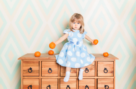 Toddler child baby girl in light blue dress seriously sitting on the wooden chest of drawers and holding fresh orange mandarins in her hands on rhomb wallpaper background. Childrens emotions feelings