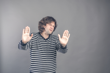 Attractive brunet male shows refusal gesture, curly man does not want to participate in meeting, says: It is not for me, leave me in piece, has angry expression, poses against grey studio background