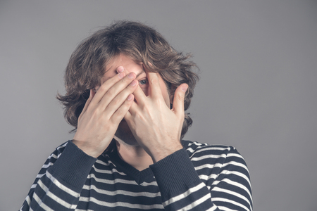 Caucasian shaggy young male in striped sweater peeks though fingers, covers face with both hands, has frightened expression as notices something terrible or scarying, isolated over grey background