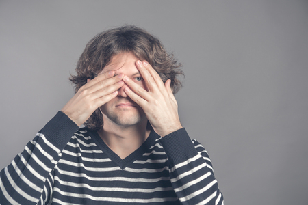 Portrait of young hipster man in sweater peeping at the camera through his fingers. Picture of embarrassed male looking through his hands covering his face isolated against studio interior background