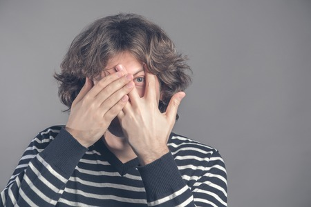 Handsome man with dark curly hair, bristle, hides face with hands, peeks through fingers, wears striped sweater, feels shy, isolated over grey background. Curious guy cannot to look at present. Reklamní fotografie