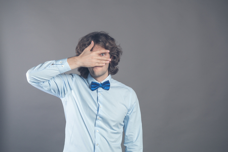 Horizontal shot of unshaven caucasian young curly male covers eyes with palm, tries to be hidden, looks through fingers, waits for permission to look at surprise, isolated over grey background