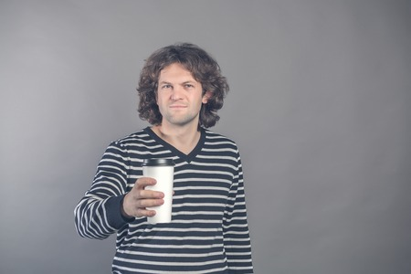 Portrait of happy handsome dark haired curly man in striped sweater with paper cup of morning coffee isolated on grey background. Good morning with tea. Takeaway coffee. Time for break. Space for text