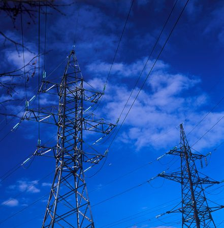 Electric power lines on a background of the blue sky. Stock Photo