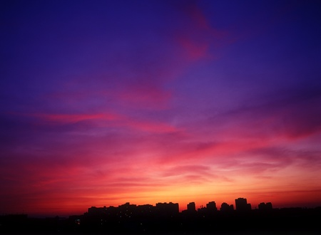 Landscape of houses silhouettes against a mystery crimson sunset.