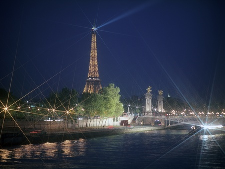 PARIS, FRANCE, APRIL 23, 2011. Paris by night; cityscape of Seine river with Eiffel Tower and Pont Alexandre III after sunset. Paris, France, April 23, 2011.