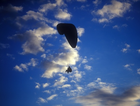 Silhouette of paraglider with two person against the cloudy blue sky.