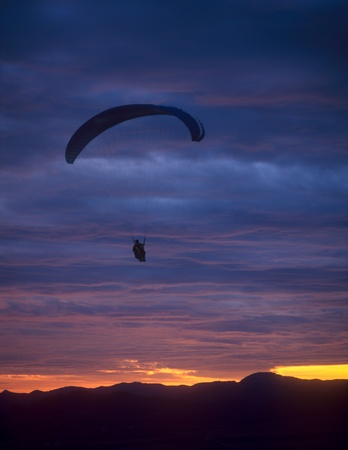 Paraglider flying against a sunset. Clementyev mountain, Crimea, Ukraine. photo