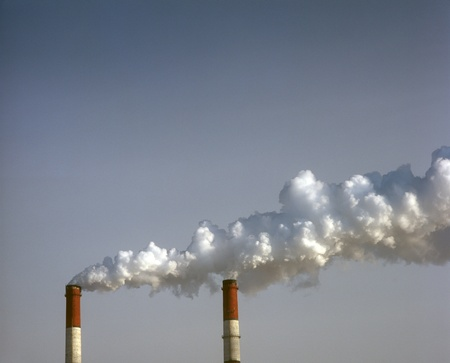 Air pollution by smoke coming out of two factory chimneys. photo