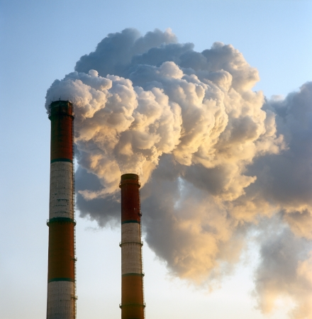 exhaust: Air pollution by smoke coming out of two factory chimneys.