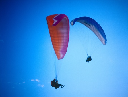 Two paragliders in the clear blue sky. photo
