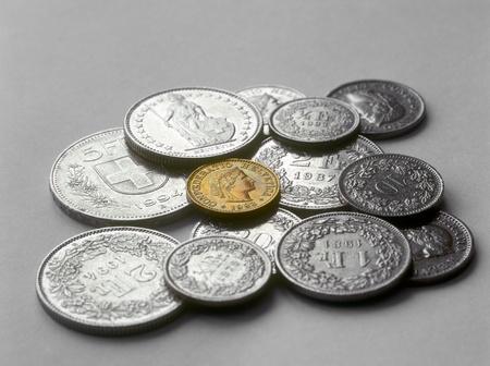 frank szwajcarski: Frank szwajcarski monety różne na szarym tle.