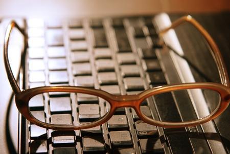 backlit keyboard: Glasses on the laptop. See similar image in my portfolio. Stock Photo