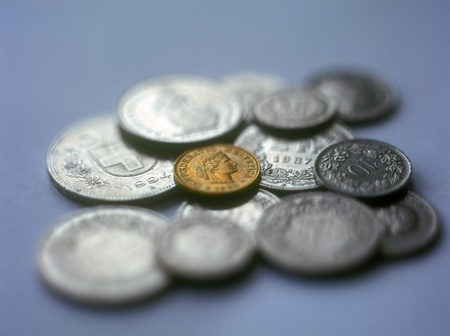 helvetica: Various swiss franc coins on the blue background with shallow depth of field. Stock Photo