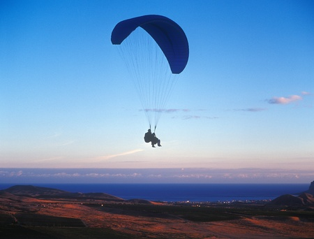 Two men soaring in a tandem paragliding flight. photo