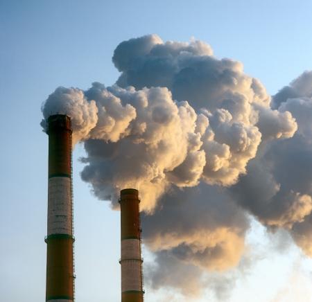 contaminacion ambiental: La contaminación del aire por el humo saliendo de dos chimeneas de la fábrica.