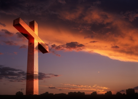 Cross on sunset background with copy space. photo