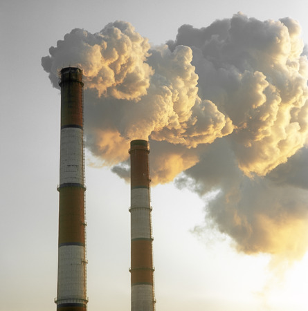 Air pollution by smoke coming out of two factory chimneys  Stock Photo