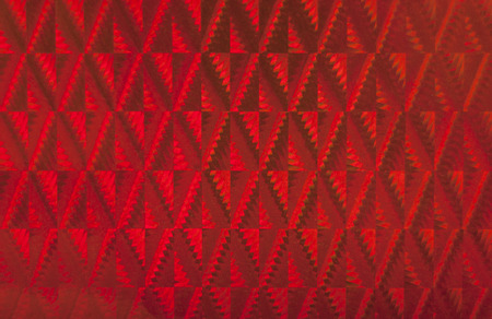 suface: Red patterned holographic surface  Useful as background  Stock Photo