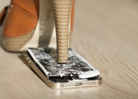 High heel shoe crushing a mobile phone