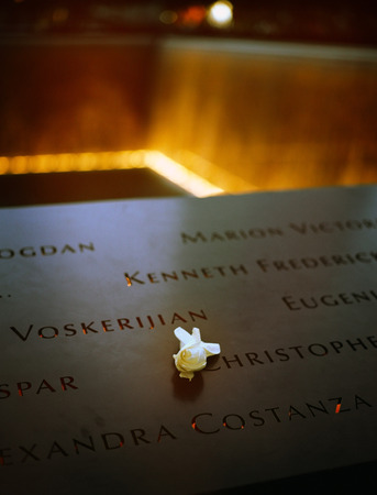 9 11: New York City, USA - June 24, 2014  9 11 Memorial at Ground Zero, Lower Manhattan, commemorating the terrorist attack of September 11, 2001  Flowers near the names of victims engraved in the bronze parapet