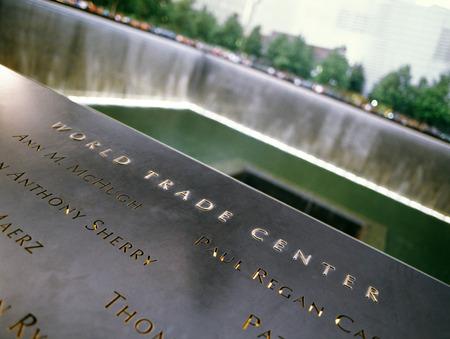 september 11: New York City, USA - June 24, 2014: 911 Memorial at Ground Zero, Lower Manhattan, commemorating the terrorist attack of September 11, 2001. Names of victims engraved in the bronze parapet.