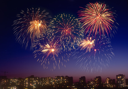 colorful sky: Beautiful firework display over a dark cityscape. Stock Photo