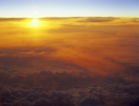 Sunset over a clouds. View from aircraft window.