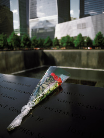 New York City, USA - June 24, 2014: 911 Memorial at Ground Zero, Lower Manhattan, commemorating the terrorist attack of September 11, 2001. Flowers near the names of victims engraved in the bronze parapet.