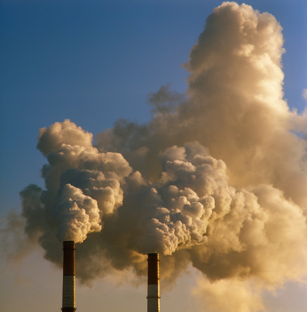 dirty environment: Air pollution by smoke coming out of two factory chimneys.