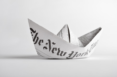 Kyiv, Ukraine - February 28, 2015: Paper boat of The New York Times newspaper on white background.