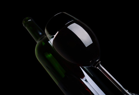 Bottle and glass of red wine on black background. photo