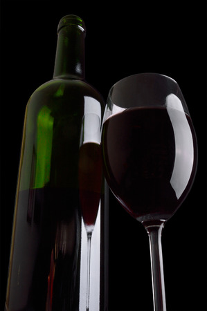 Bottle and wineglass of red wine on black background. photo