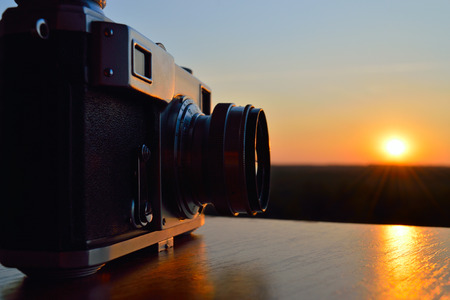 rangefinder: Classic rangefinder vintage camera against a sunset sky. The picture symbolizes the sunset era of film photography.