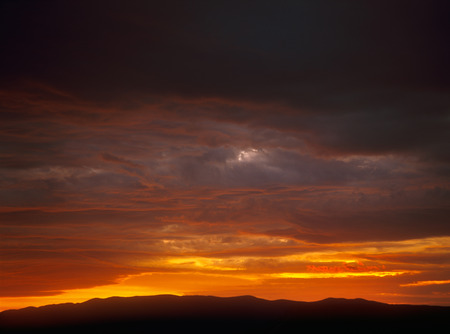 ominous: Ominous dramatic sunset over a dark landscape.