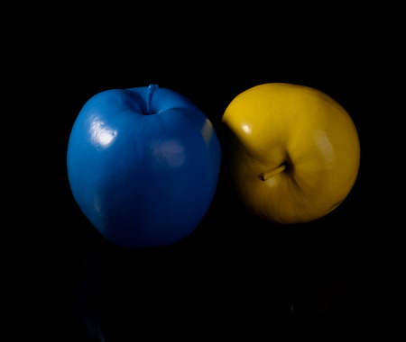 Yellow apple and blue apple on black background.