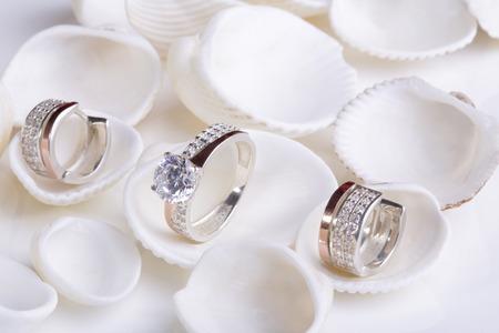 seashell: Beautiful gold ring and earrings with diamonds on white seashells. Stock Photo