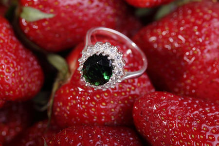 green gemstone: Beautiful gold ring with green gemstone and small diamonds on a red strawberry.