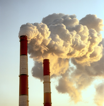 Air pollution by smoke coming out of two factory chimneys.