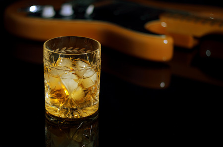 whiskey on the rocks: A glass of whiskey on the rocks and old guitar.