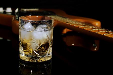 gitara: Kieliszek whisky na skałach i starej gitarze. Zdjęcie Seryjne