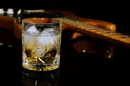 whisky: Un verre de whisky sur les rochers et vieille guitare. Banque d'images