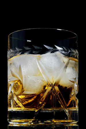 whiskey on the rocks: A glass of whiskey on the rocks on black background